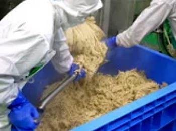 蒸し上がると直ぐに大豆は潰されます。